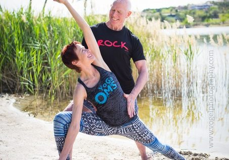 Greg assists Susan in side angle pose